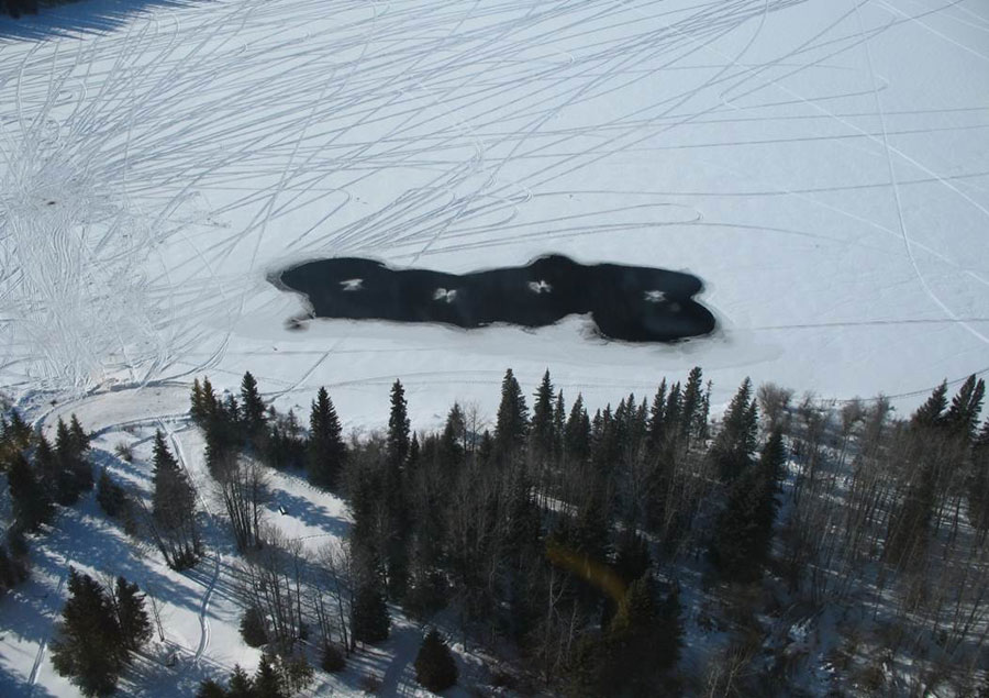 Open water on an aeration project with dozens of snowmobile tracks nearby
